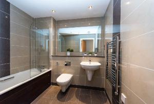 Badkamerrenovatie grijze glanzende tegels