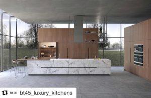 Grote open loft keuken. houte panelen met marmer eiland met houte werkblad