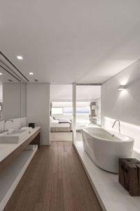 Witte badkamer met zacht houten vloer en bedmeubel